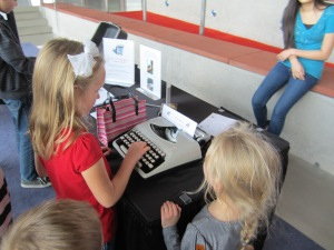 Isabella types a message on a typewriter in the lobby. This is part of Childsplay's 360 Degree Activities.