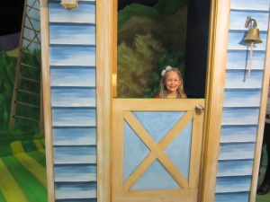 Isabella peaking out of Farmer Brown's house.